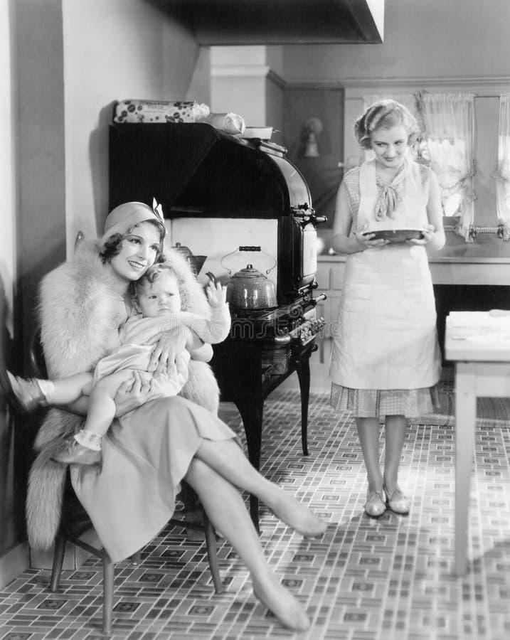 La femme élégante s'asseyant avec son bébé dans une cuisine tandis qu'un ami apporte un tarte (toutes les personnes représentées  images stock