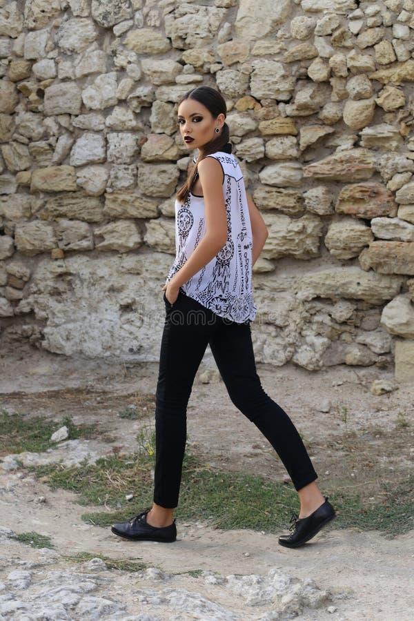 La femme élégante sexy avec les cheveux foncés utilise la chemise blanche et le pantalon noir image libre de droits