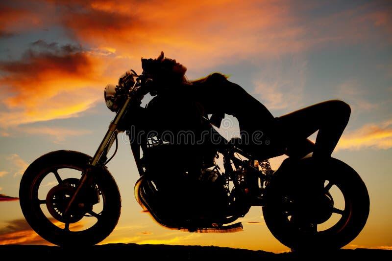 La femme étendue dessus soutiennent de la silhouette de moto images stock
