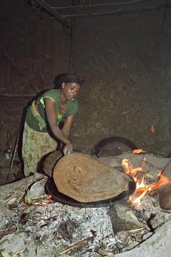 La femme éthiopienne fait l'injera cuire au four sur le feu en bois images libres de droits