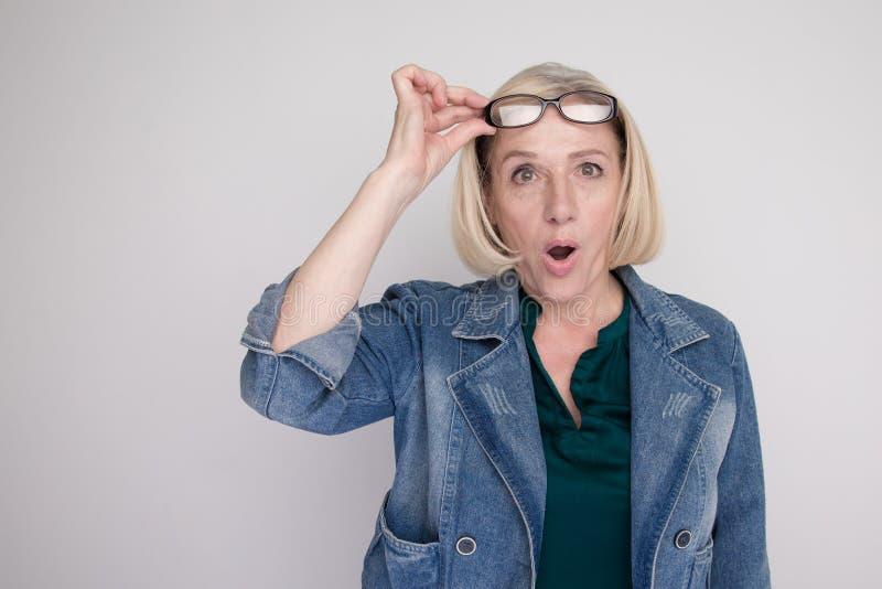 La femme étonnée adulte a ouvert sa bouche et a mis ses verres d'isolement image stock
