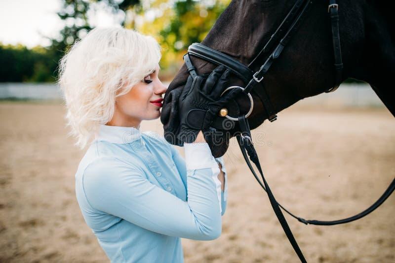 La femme étreint son cheval, amitié, équitation photo libre de droits