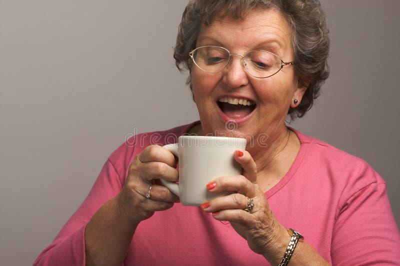 La femme aînée apprécie une cuvette de café photos libres de droits