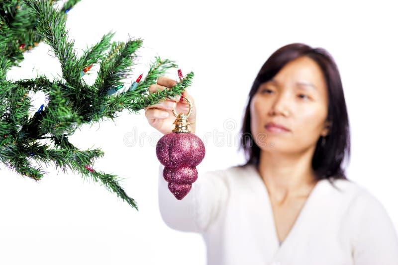 La femme accroche l'ornement de Noël. image libre de droits