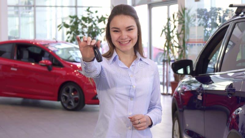 La femme achète la nouvelle voiture au concessionnaire images libres de droits