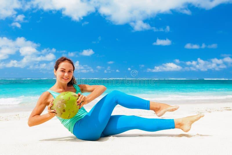 La femme active faisant des sports s'exerce avec des noix de coco sur la plage de mer photos libres de droits