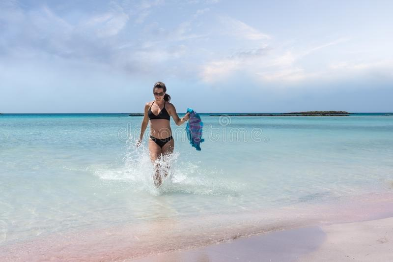 La femme adulte appréciant la turquoise de mer arrose à la plage d'Elafonisi photo libre de droits