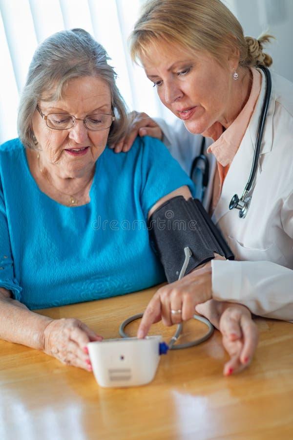 La femme adulte supérieure apprend du docteur féminin à prendre la tension artérielle photographie stock libre de droits
