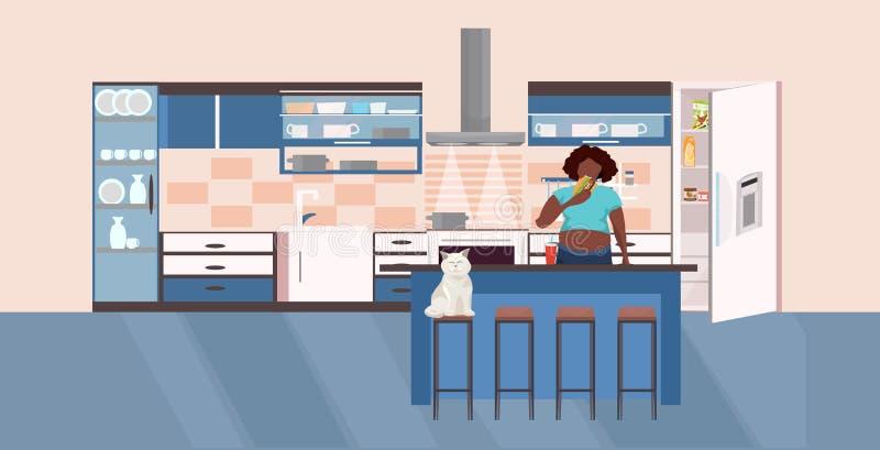 La femme affamée d'afro-américain mangeant l'hamburger près de la fille de poids excessif de réfrigérateur de concept malsain ouv illustration stock