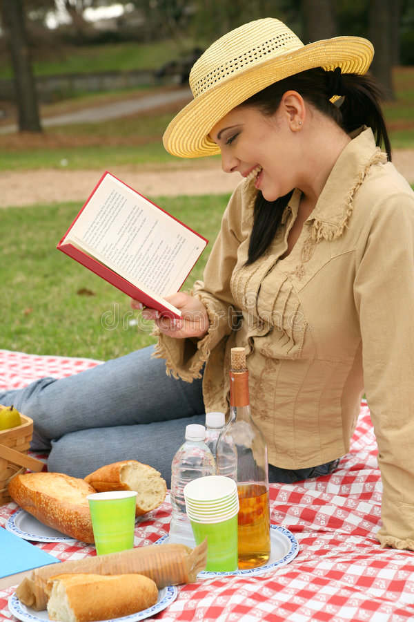 La femme a affiché le livre et apprécier le pique-nique extérieur image libre de droits