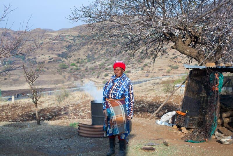 La femme africaine dans des vêtements couvrants traditionnels brasse la boisson nationale dans le baril à la cour de village, vie photographie stock