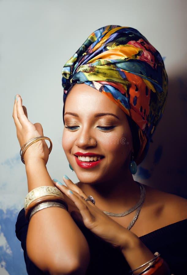 La femme africaine intelligente de beauté avec créatif composent, châle sur la tête comme le sourire cubian de plan rapproché photo libre de droits