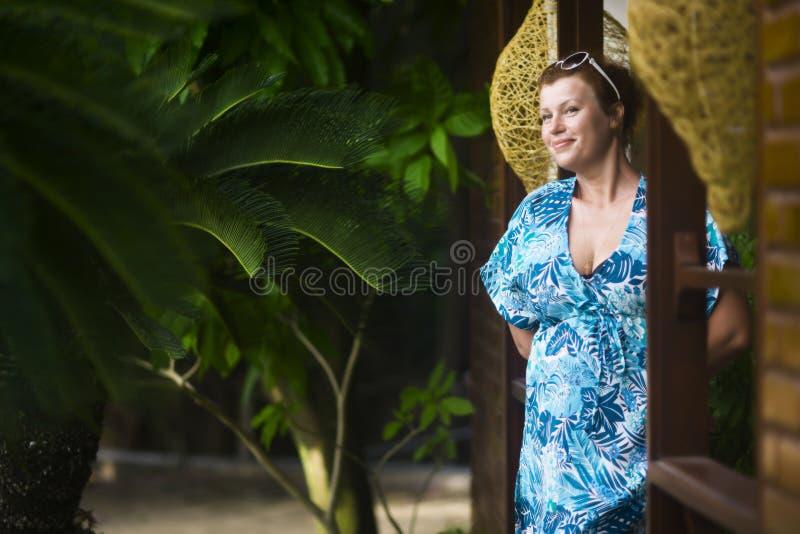La femme agée adulte dans une robe bleue se tient à la porte de sa maison pendant l'été contre les palmiers et le W images stock