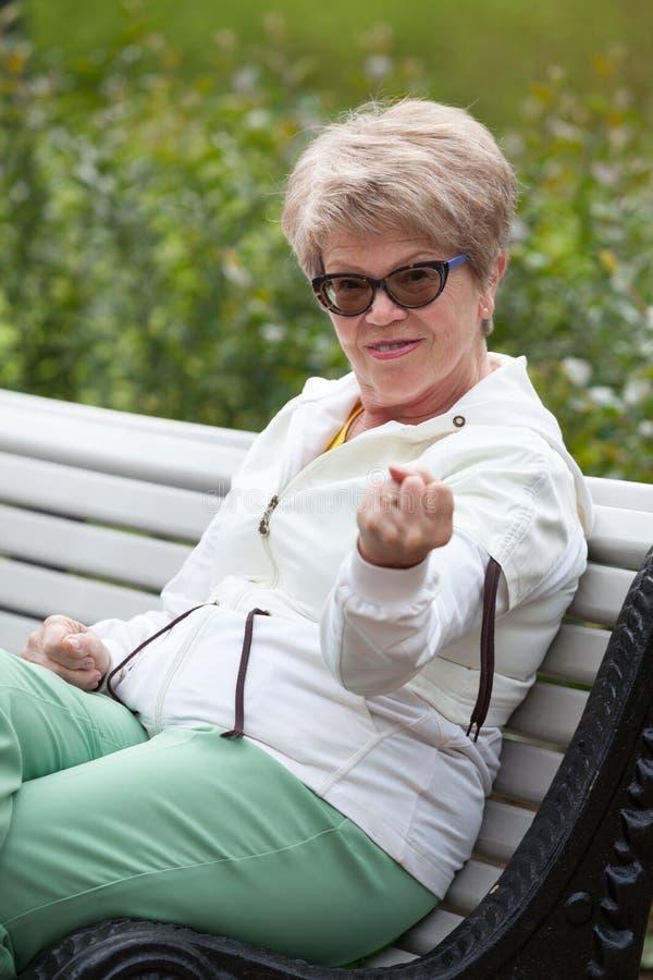 La femme agée agressive est menacée par un poing tout en se reposant sur le banc de parc photos stock