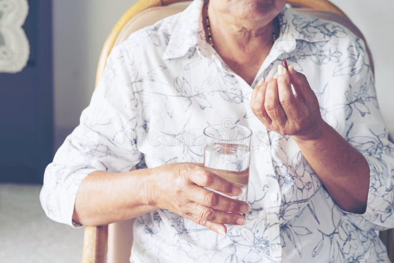 La femme agée asiatique sont prenante et mangeante des médecines et des vitamines photos stock