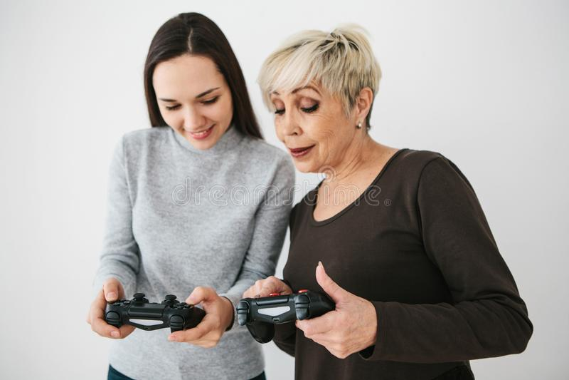 La femme agée demande à la jeune fille comment utiliser la manette pour des jeux vidéo et montre son doigt sur les boutons images libres de droits