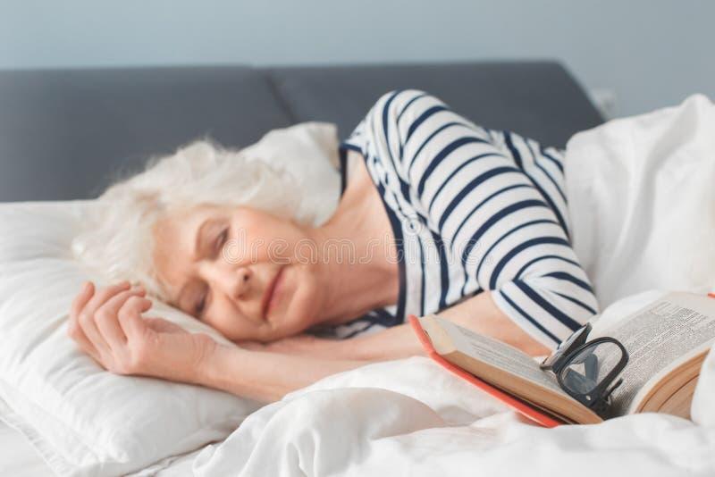 La femme agée est tombée endormi après lecture du livre photo stock