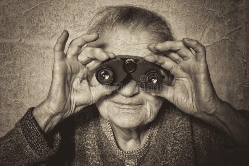 La femme agée regarde par des jumelles. photos stock