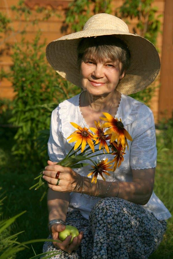 La femme agée s'assied avec peu de fleurs de rudbeckia photo libre de droits
