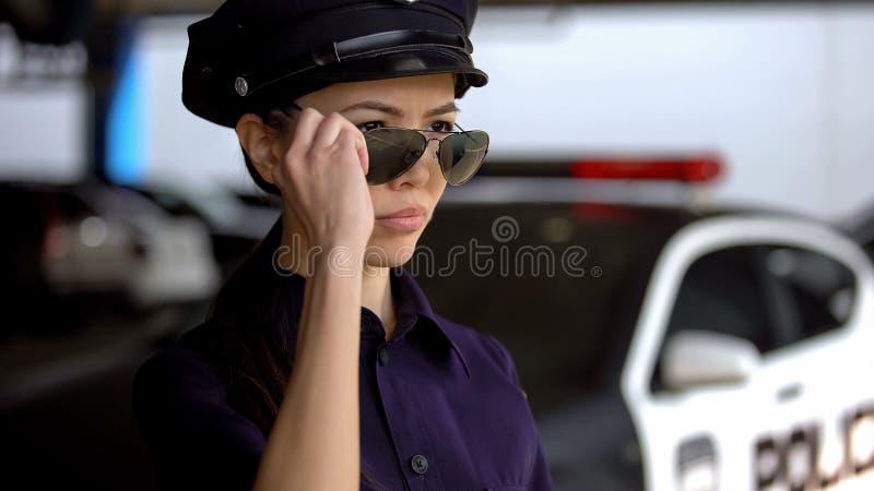La femme agent de police sérieuse dans l'uniforme de police mettant sur des lunettes de soleil, préparent pour le devoir image libre de droits