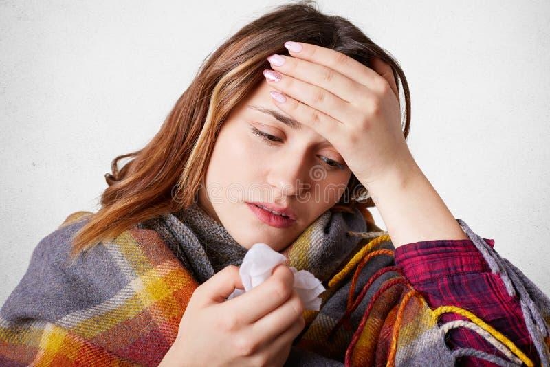 La femme allergique a le mal de tête en raison du nez bloqué, garde la main sur le front, a la haute température, se sent souffra photos stock