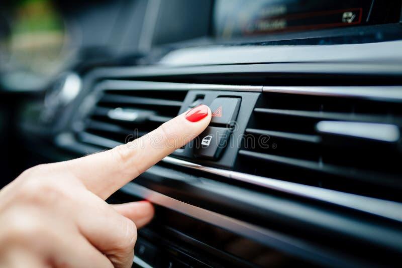 La femme allume les lumières de secours dans la voiture image libre de droits