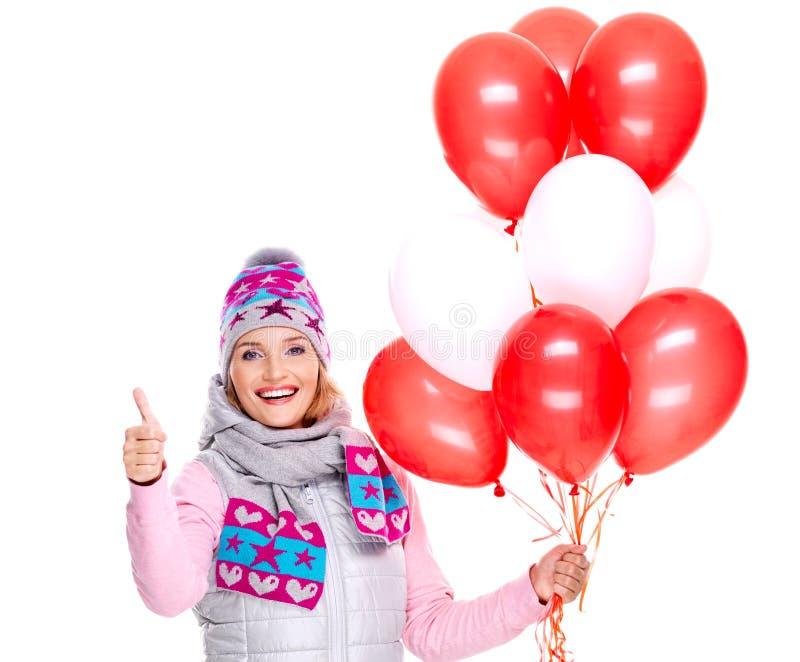 La femme américaine heureuse avec les ballons rouges et les pouces lèvent le signe image libre de droits