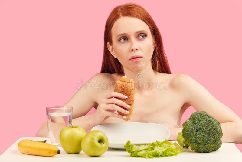 La femme apathique ennuyée mange le croissant regardant fixement dans l'espace ignorant les fruits crus photos stock