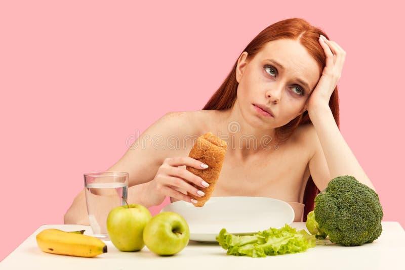 La femme apathique ennuy?e mange le croissant regardant fixement dans l'espace ignorant les fruits crus images libres de droits