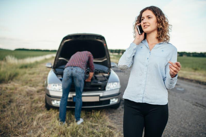 La femme appelle pour entretenir, équiper la voiture cassée par réparation photos libres de droits
