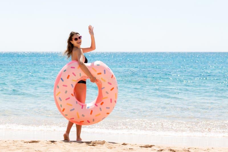 La femme appelle pour nager en mer et ondule sa main Fille d?tendant sur l'anneau gonflable ? la plage Vacances d'?t? et vacances photos stock