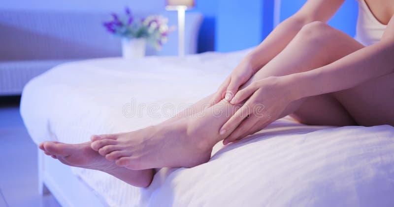 La femme appliquent la crème avec la jambe photographie stock libre de droits
