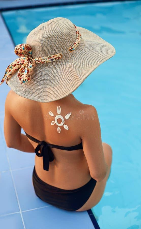 La femme appliquent la protection de crème du soleil sur l'épaule bronzée Soin vieillissant de corps de protection du soleil de s image libre de droits
