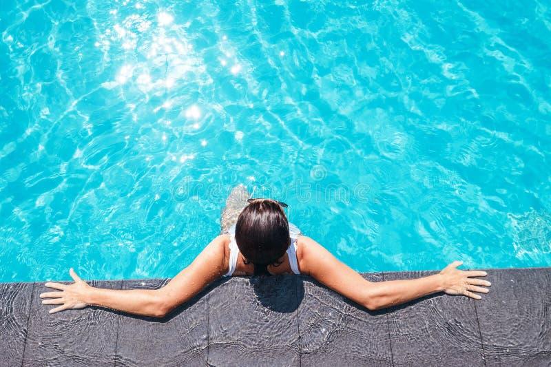 La femme apprécient le soleil dans la piscine photographie stock libre de droits
