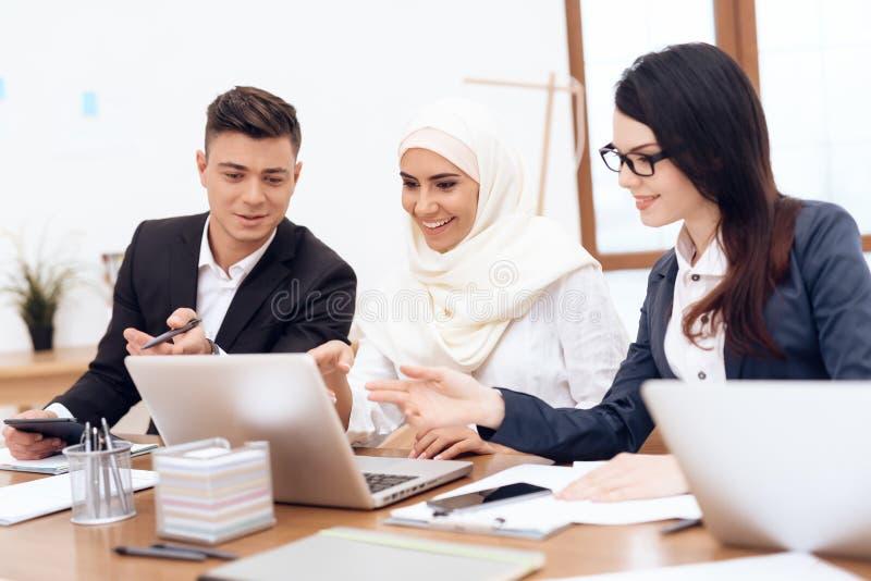 La femme arabe dans le hijab travaille dans le bureau ainsi que ses collègues photo libre de droits