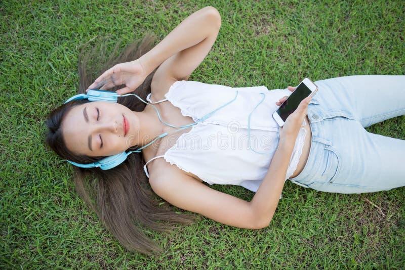 La femme asiatique écoutent musique sur l'herbe images stock