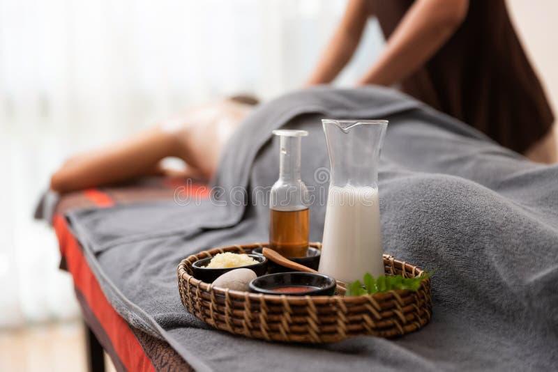 La femme asiatique appréciant un sel frottent le massage à la station thermale photographie stock