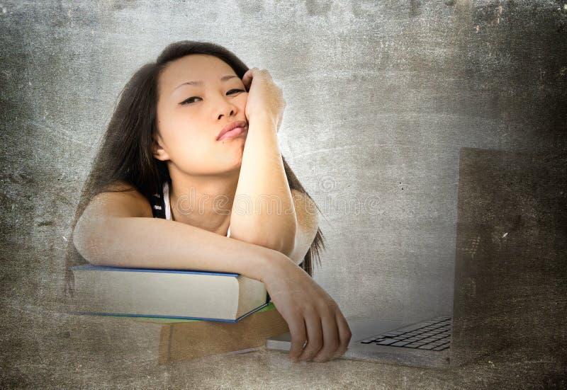 La femme asiatique assez chinoise d'étudiant de jeunes avec l'ordinateur a ennuyé le penchement fatigué et surchargé sur l'étude  images libres de droits