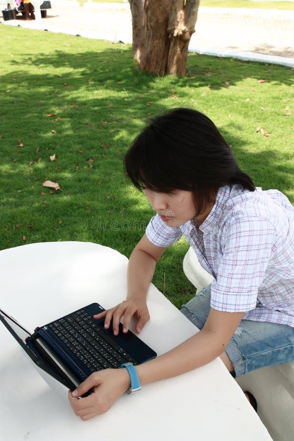 La femme asiatique attirante est à l extérieur avec l ordinateur portatif