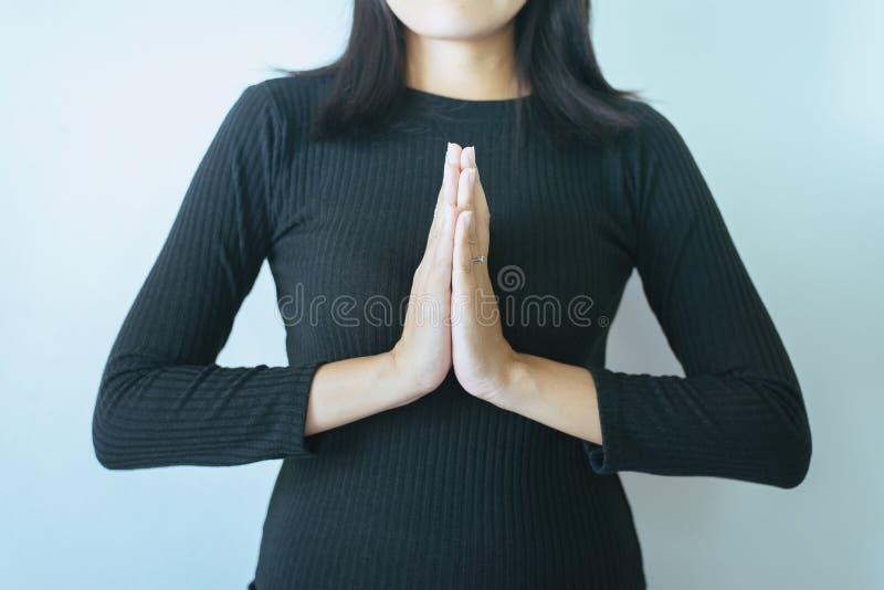 La femme asiatique avec la main en position de prière de culte, les mains femelles de prière a étreint ensemble photographie stock