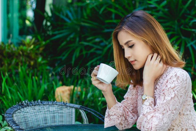 La femme asiatique d'affaires est travaillante et buvante du café au temps de détente photo libre de droits
