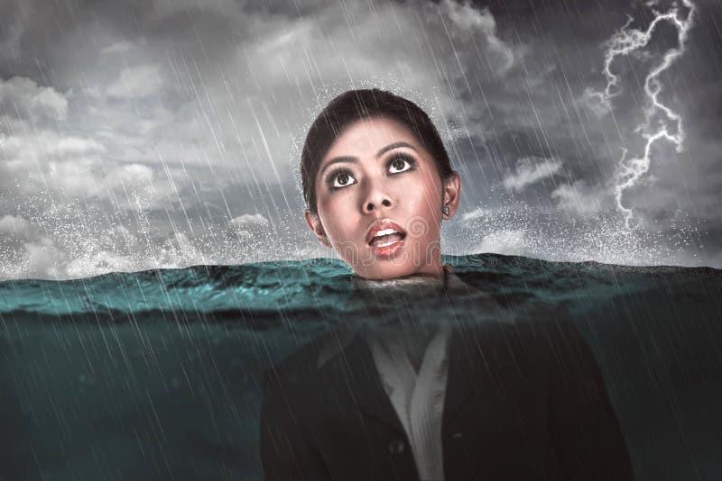 La femme asiatique d'affaires se noient au milieu de la mer photographie stock libre de droits