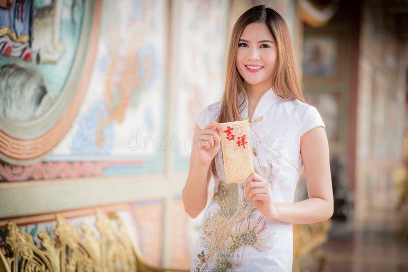 La femme asiatique dans le Chinois habillent juger le couplet 'heureux' (Chine photographie stock libre de droits