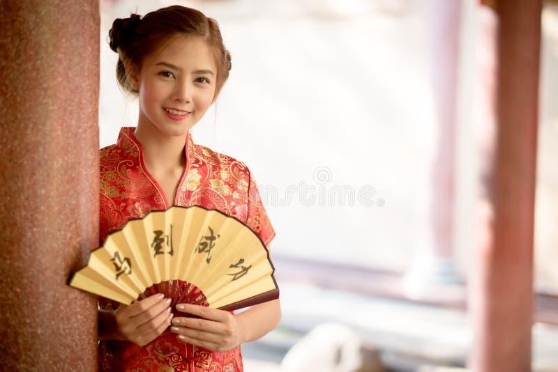 La femme asiatique dans le Chinois habillent tenir le couplet 'succès' (Chin images stock