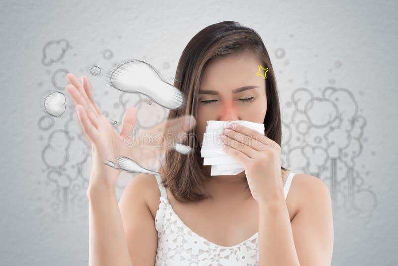 La femme asiatique dans la robe blanche attrapent son nez en raison d'une mauvaise odeur images stock
