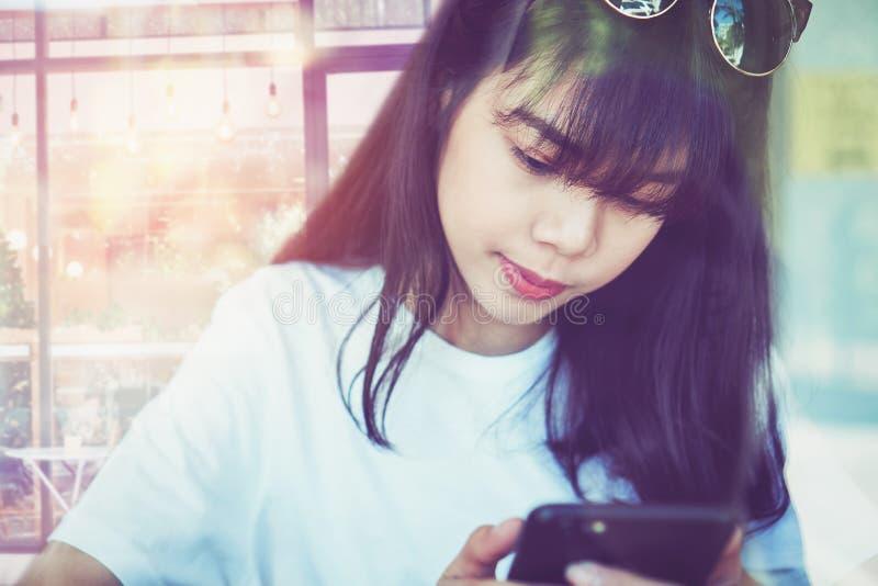 La femme asiatique dans un café touche l'écran de smartphone, utilisant envoient un message à une application sociale de media d' image libre de droits