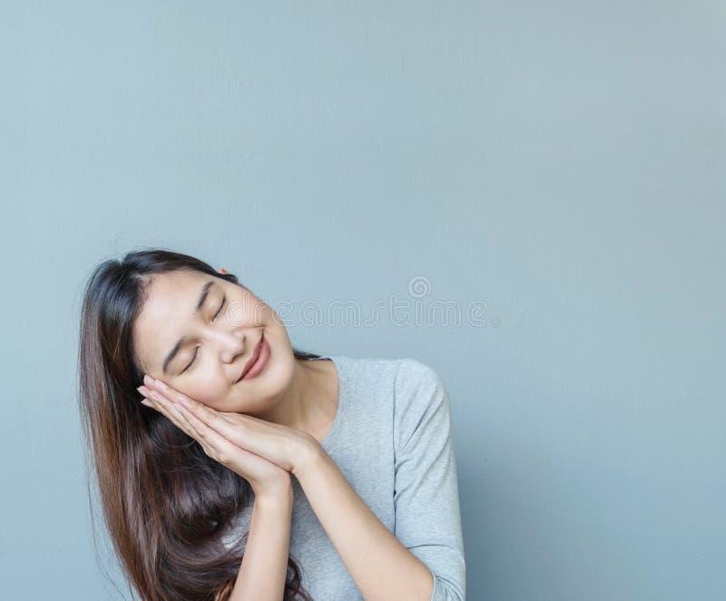 La femme asiatique de plan rapproché dans l'action de sommeil avec le rêve doux sur le mur brouillé de ciment a donné au fond une photo libre de droits