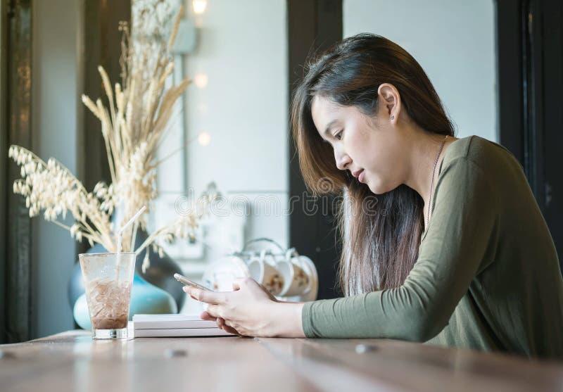 La femme asiatique de plan rapproché emploient un téléphone intelligent et un chocolat glacé potable au contre- bureau en bois da photos stock
