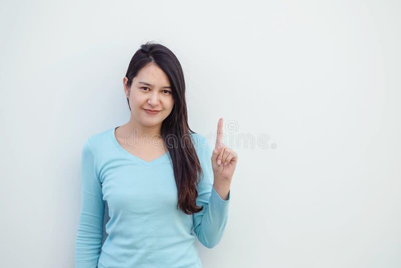 La femme asiatique de plan rapproché retardent un mouvement de doigt avec le visage de sourire sur le fond de mur de ciment blanc image stock