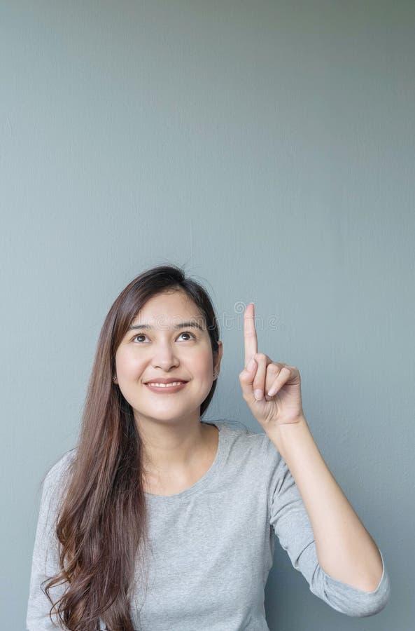 La femme asiatique de plan rapproché retardent un point de doigt à l'espace avec le visage de sourire sur le fond texturisé par m photo libre de droits